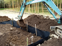 ある程度シートを広げ設置が完了したら土を埋め戻す。この場合、勢い良く埋め戻すとシートがよれてしまうので静かに土を踏み固めながら土を戻す。