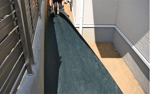 整地後、端部からグリーンビスタ®プロ防草・砂利下シートを敷設します。